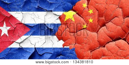 Cuba flag with China flag on a grunge cracked wall