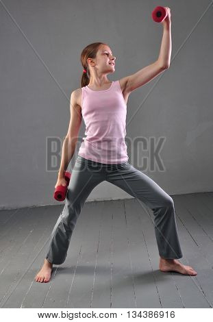 Teenage sportive girl is doing exercises to develop with dumbbells muscles isolated on grey background. Sport healthy lifestyle concept. Sporty childhood. Teenager exercising and posing with weights.