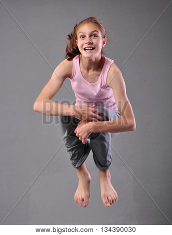 Healthy young happy smiling teenage girl dancer skipping jumping and dancing in grey studio. Child exercising. Sport healthy lifestyle concept. Sporty childhood. Isolated over grey background.