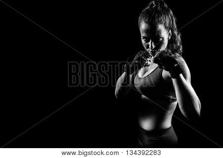 Portrait of woman with fighting stance against black background