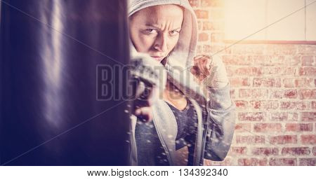 Portrait of female fighter in hood with fighting stance against gym