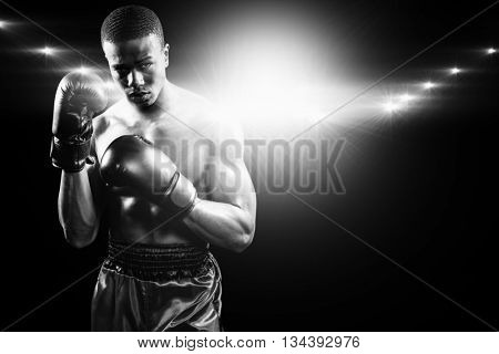 Portrait of boxer performing uppercut against black background