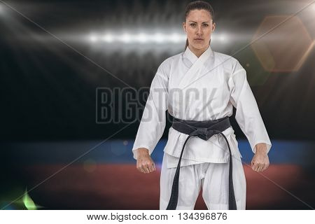 Female karate player posing on white background against composite image of playing field indoor