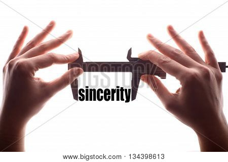 Color horizontal shot of two hands holding a caliper and measuring the word