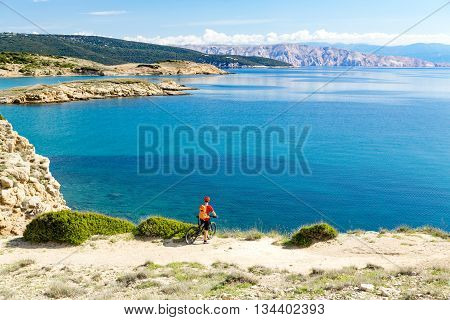 Mountain biker looking at view and traveling on bike in summer sea landscape. Man rider cycling MTB on country road or single track. Fitness motivation inspiration in beautiful inspirational view.