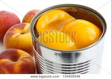 Detail Of Open Can Of Peach Halves In Syrup On White Background With Whole Fresh Peaches.