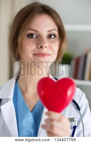 Female medicine doctor hold in hands red toy heart closeup. Cardio therapeutist physician make cardiac physical heart rate measure or arrhythmia concept