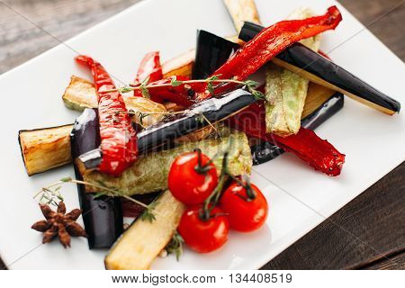 Grilled vegetables on white plate. Close-up of white plate with grilled vegetable strips. Grilled paprika, eggplant and vegetable marrow with cherry tomato on white plate top view.