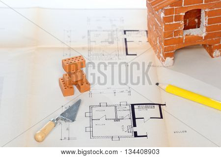 some tools and bricks on a blue print