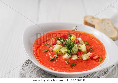Vegetable soup gazpacho stand bread slices on white boards horizontal