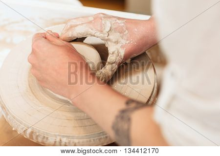 Potter hands shaping clay top view. Closeup on artisan hands making pottery. Art therapy process