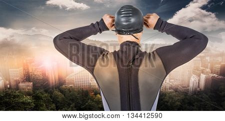 Rear view of swimmer in wetsuit wearing swimming goggles against trees and mountain range against cloudy sky