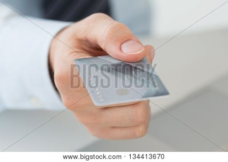 Close up view of business man hand holding credit card. Online payments e-commerce internet banking shopping delivery anti-fraud or financial security concept.