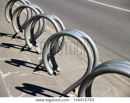 Empty Metal Bicycle Parking Rack on the sidewalk brightly lit with deep shadow