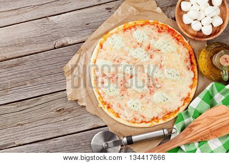 Quattro fromaggi pizza on wooden table. Top view with copy space