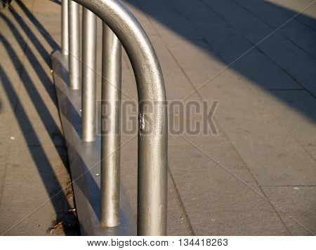 Empty Metal Bicycle Parking Rack on the pavement at evening light closeup