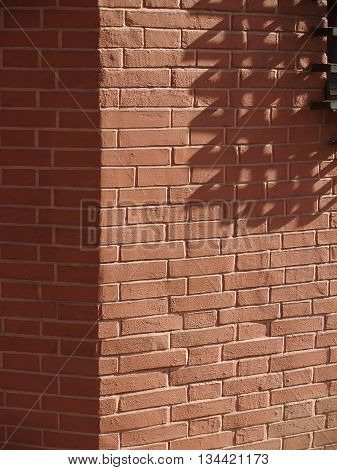 Sunlit red brick wall corner with iron ladder shadow. Abstract geometric composition