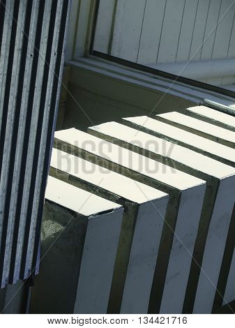 Abstract geometric composition formed by the deep shadows and bright light contrast on different textured surfaces of buildings