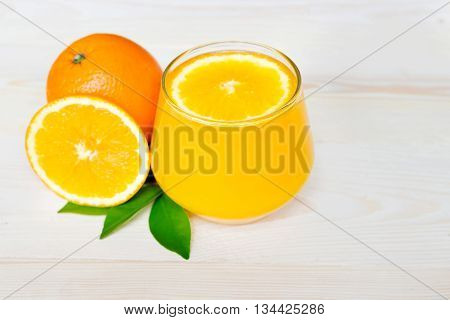 Navel orange juice and slices of orange with leaves on wooden background