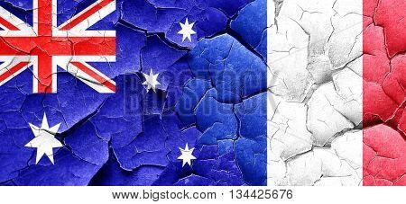 Australia flag with France flag on a grunge cracked wall