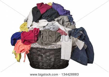 Dirty laundry piled up overflowing in a black basket isolated on white.