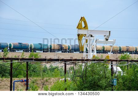 Pump jack well head and pipeline on the background of moving tank train. Oil and gas concept.