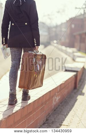 Urban young girl walking down the street and carrying suitcase