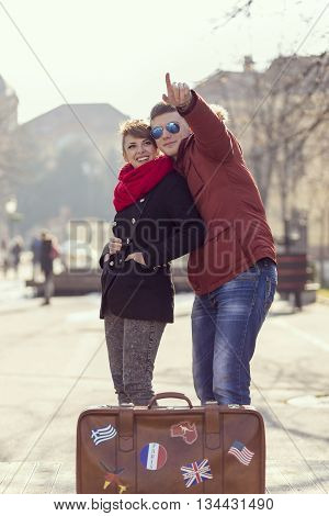 Couple in lovehugging sightseeing and standing next to a suitcase