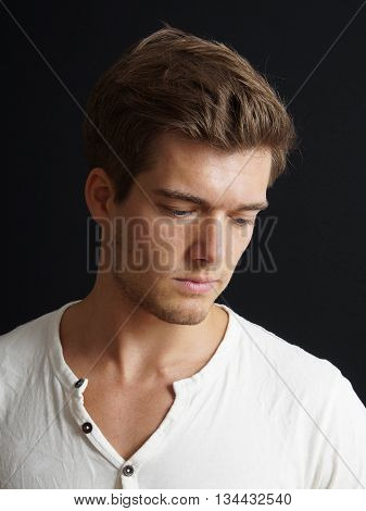 introverted young man looking down on black