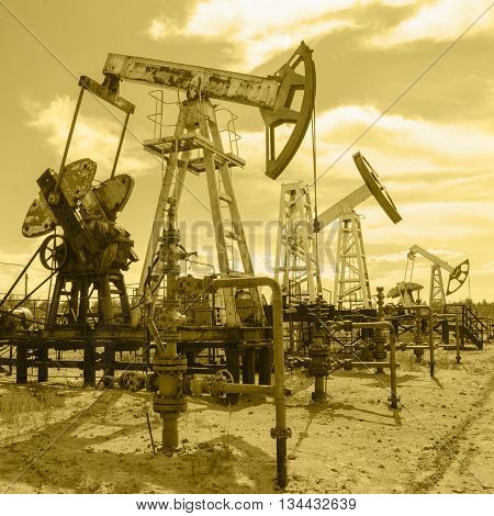 Group of pump jack and wellhead in the oilfield. Oil and gas concept. Toned.