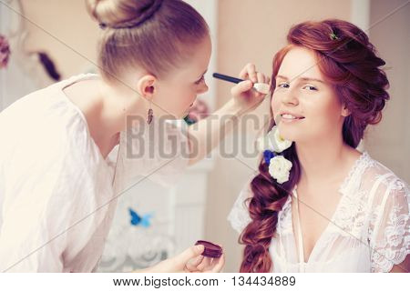 Stylist makes makeup bride on the wedding day poster