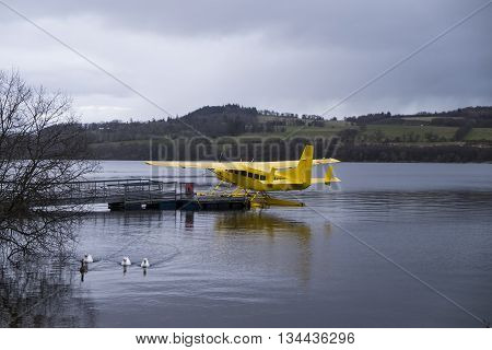 Loch Lomond Scotland - 1 APRIL 2015 - Bright yellow Loch Lomond Seaplane moored on Loch Lomond beside Cameron House Hotel under dull grey April skies.