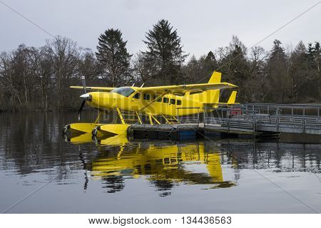 Loch Lomond Scotland - 2 April 2015 - Yellow Loch Lomond Seaplane reflected in the loch at its mooring on Loch Lomond beside Cameron House Hotel
