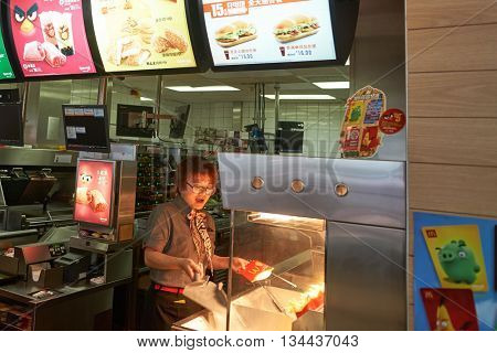 SHENZHEN, CHINA - MAY 06, 2016: worker in McDonald's restaurant. McDonald's is the world's largest chain of hamburger fast food restaurants, founded in the United States.