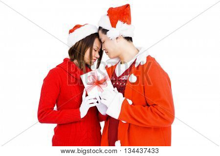 Young couple in christmas attire holding gift on white background