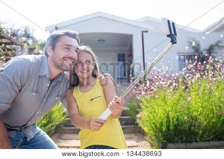 Father and daughter in garden taking a selfie with selfie stick