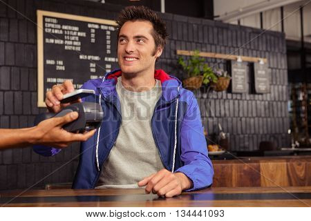 Man using mobile payment in a coffee shop