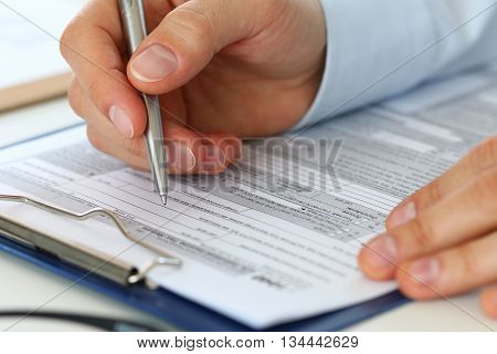 Close up of male accountant filling tax form. Man writing something sitting at his office. Filling individual income tax return form 1040 making financial report home finances or economy concept