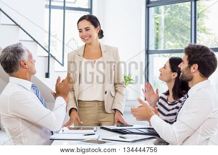A businesswoman is standing in front of her colleagues who are applauding at work