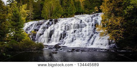 Michigan's Bond Falls Panorama. Beautiful Bond Falls in Michigan's Upper Peninsula surrounded by autumn foliage.