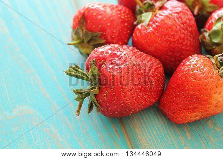 Strawberries on wooden blue desk. Stock photo.