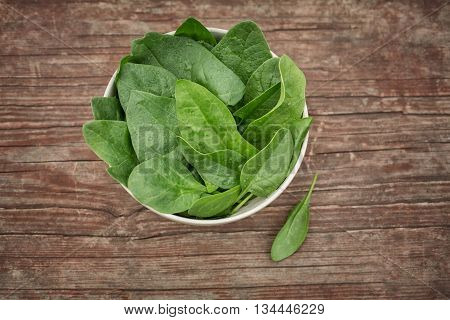Bowl of fresh spinach leaves on wooden table, in the garden. Spinach leaves closeup. Spinach - Healthy food. Food background