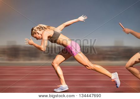 Sporty woman running on a white background against digital image of an athletic track