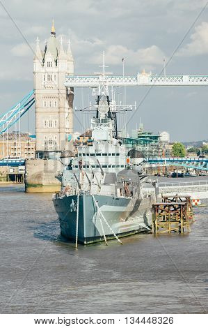 LONDON UK - MAY 12 2011: View of HMS Belfast and in background Tower bridge. Belfast moored in London on River Thames and operated by Imperial War Museum.