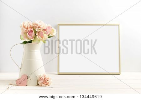 Mockup styled stock photograph of cream jug of flowers next to a Gold frame. You can place your business promotion blog title quote headline or image in the frame.