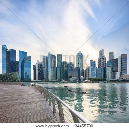 Singapore central quay with reflection decks on foreground. Modern city architecture at sunrise.