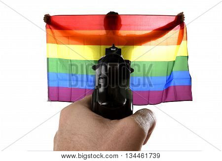 intolerance and violent representation of terrorist attack with close up hand holding gun pointing on proud gay man spreading wide big pride homosexual flag