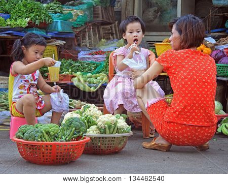 Woman With Childrens On Street Market In Hue, Vietnam