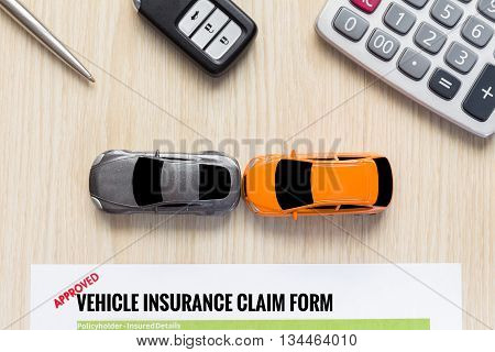 Top view of approved vehicle insurance claim form with car toy crash on wooden desk concept