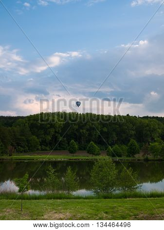 Hot air balloon over the like and forest